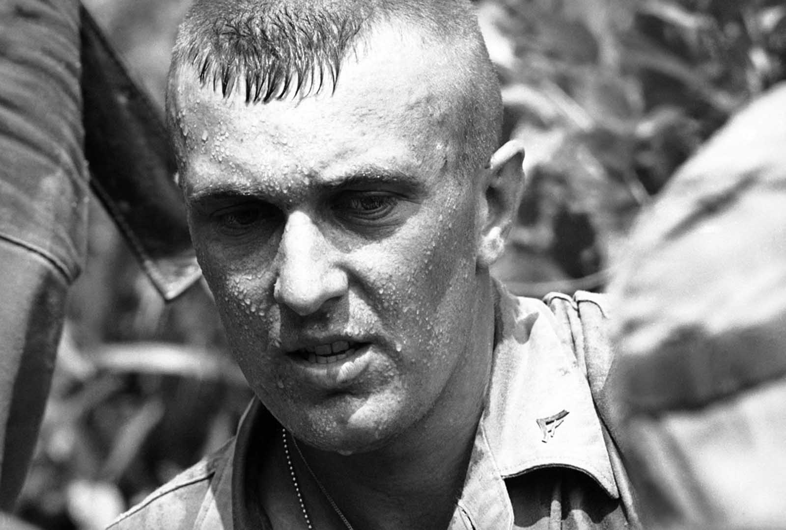 A U.S. Marine, newly arrived in South Vietnam on April 29, 1965, drips with perspiration while on patrol in search of Viet Cong guerrillas near Da Nang air base. American troops found 100-degree temperatures a tough part of the job. General Wallace M. Greene Jr., a Marine Corps commandant, after a visit to the area, authorized light short-sleeved uniforms as aid to troops' comfort.