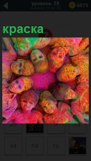 На розовом полу лежат головы детей друг к другу в круг и все в краске разноцветной