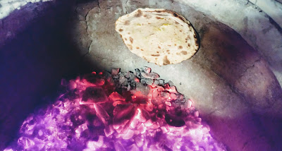 Cooking aloo paratha in charcoal Tandoor