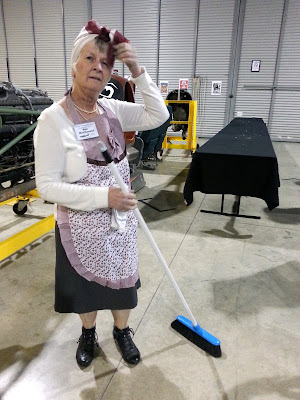 A woman dressed as char lady poses with her broom in front of an empty table.