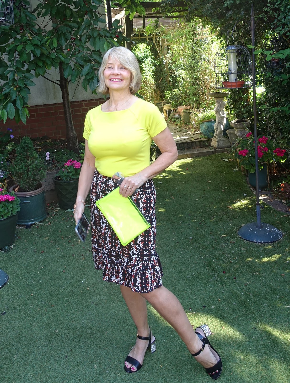 Acid yellow tee worn with geometric patterned knee-length skirt from TU at Sainsbury's