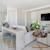 Sala branca com toques de azul claro e dourado + aparador com puffs atrás do sofá!