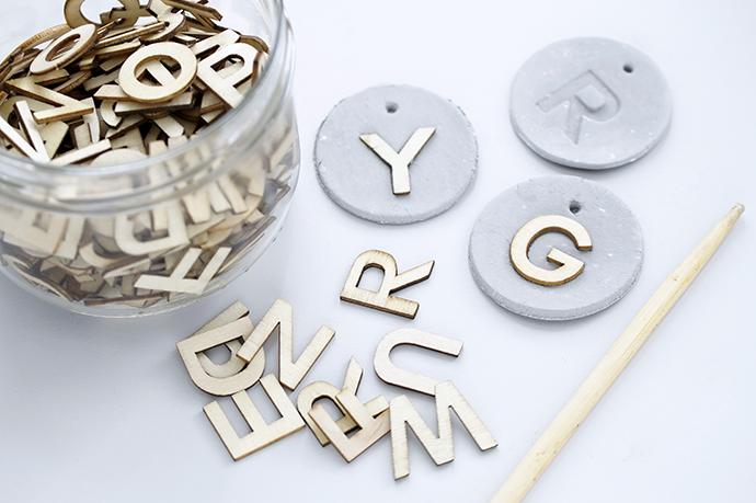 Kleine Holzbuchstaben in die weiche Modelliermasse gedrückt