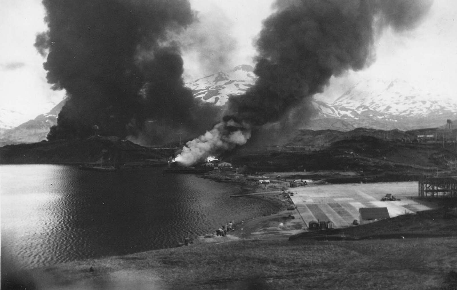 Oil tanks, the SS Northwestern, a beached transport ship, and warehouses on fire after Japanese air raids in Dutch Harbor, Alaska, on June 4, 1942.