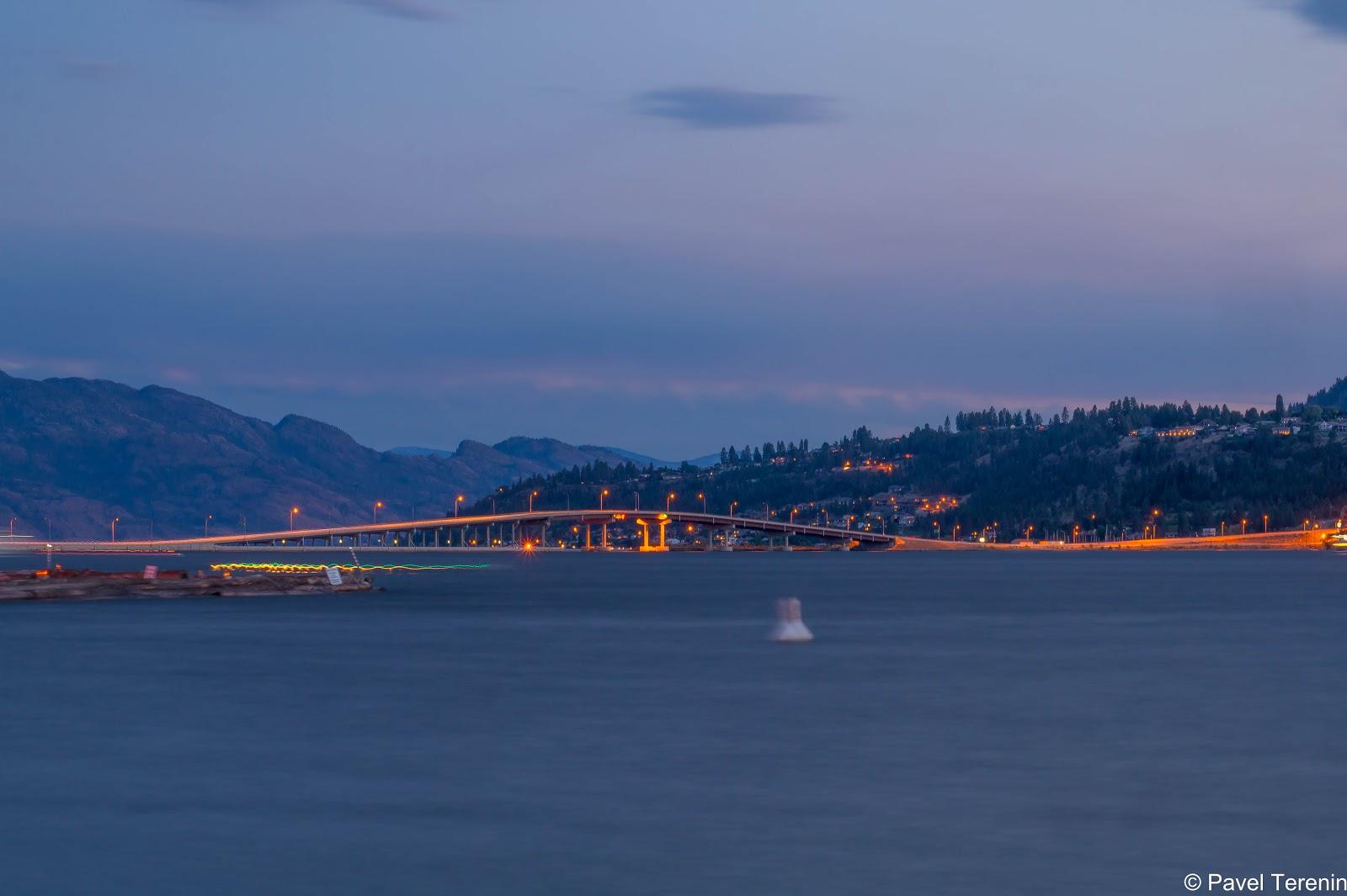 По мосту через озеро Оканаган проносятся автомобили, прочерчивая своими фарами яркие полоски света.