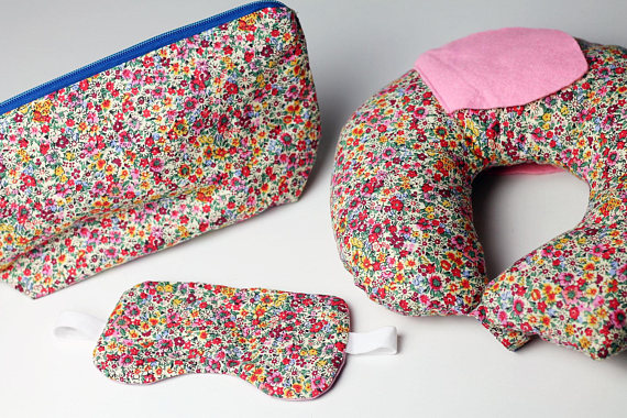 a neck cushion, eye mask, and makeup bag in colourful floral print