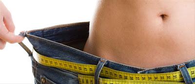 pessoa que emagreceu e está segurando a calça larga, com uma fita métrica na cintura