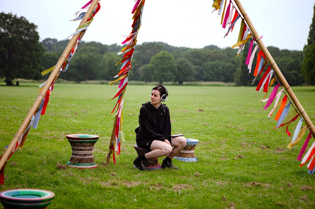 """""""A young white woman is in a large park, sitting on one of several small colourful stools. She is listening to the audio trail on large headphones and looking at the silk bunting fluttering in the breeze."""