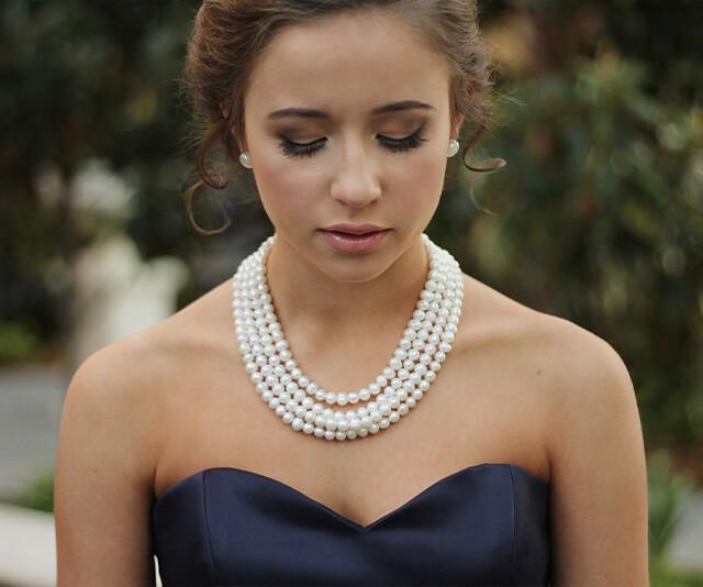 mulher usando um colar de perolas como acessorios classico da moda