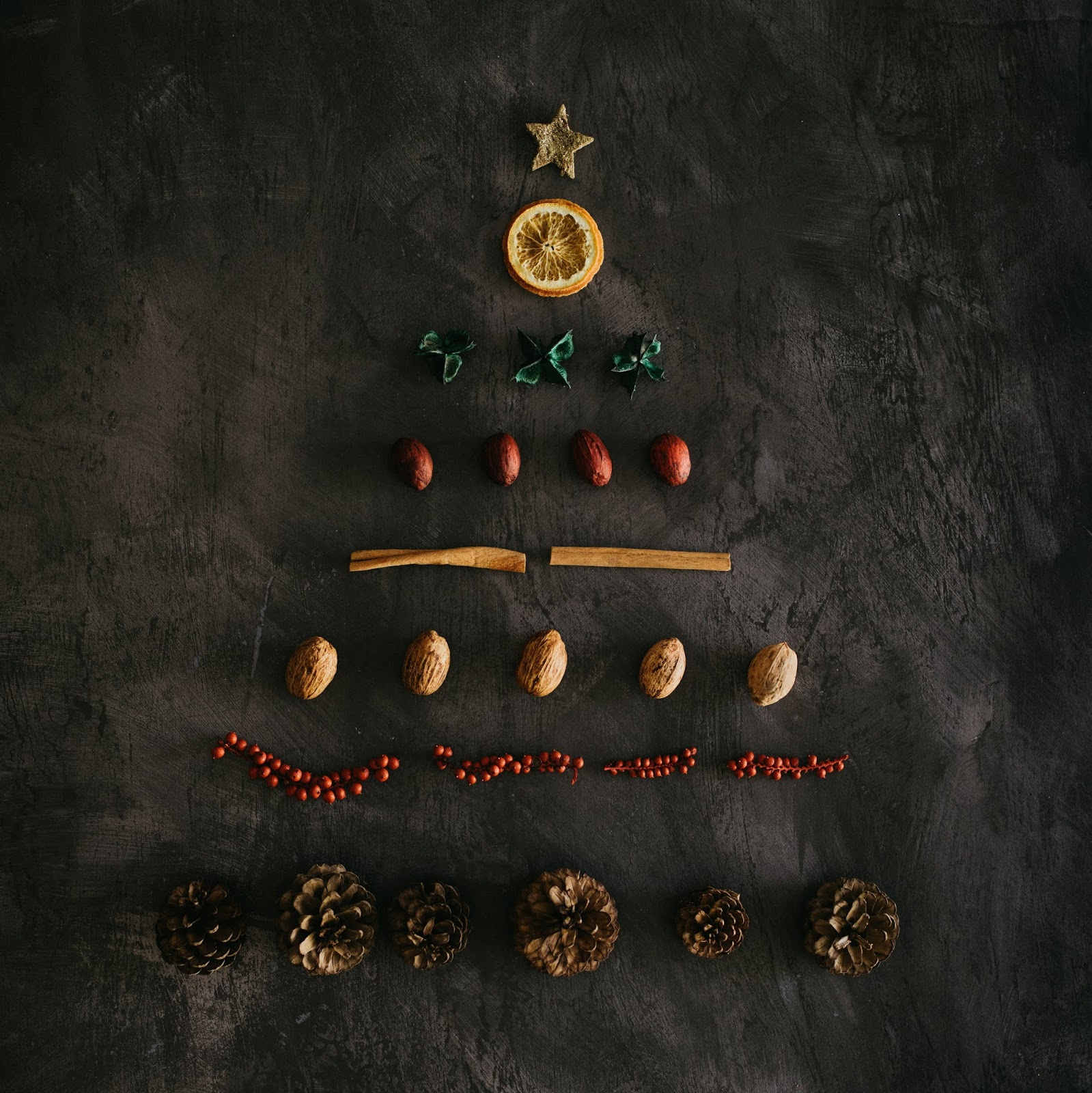 A photo taken from above of the shape of a Yule tree laid out on a black board-esque surface, made from a star cookie, a dried orange slice, evergreen leaves, brown nuts, cinnamon sticks, walnuts, strings of red berries, and pinecones.
