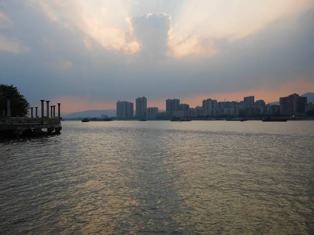 sun setting behind clouds over the Beijiang River in Qingyuan