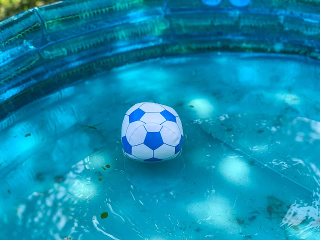 a small soft football with foam inside in a dirty paddling pool