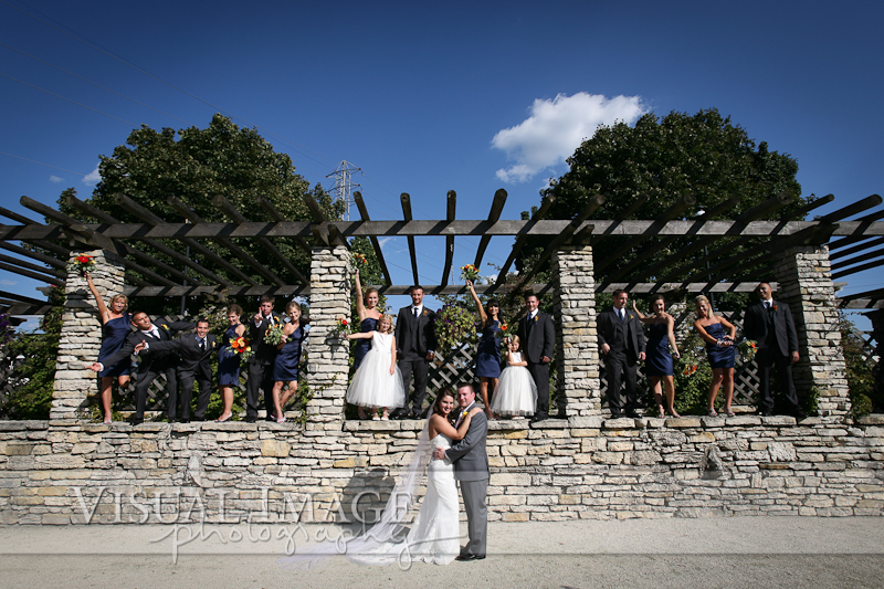 Bridal party portrait in formal gardens at Frame Park standing on rock wall