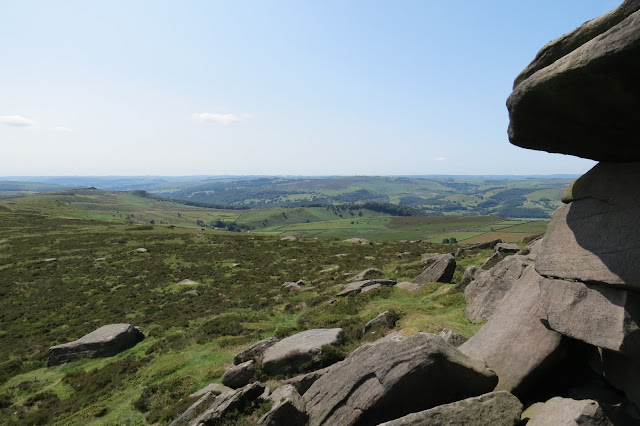 A view from the gritstone escarpment across moorland to rolling hills and valleys.