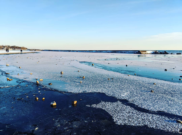 Frozen lake with snow on top and a blue sky in the background