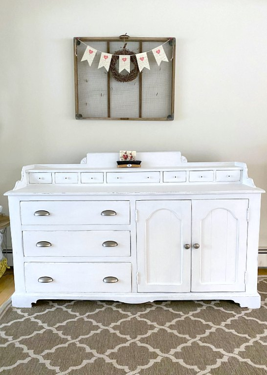 Farmhouse sideboard with sifting bin on wall above.