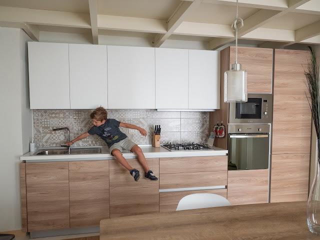 Niño sentado en la encimera de la cocina en blanco y madera clarita