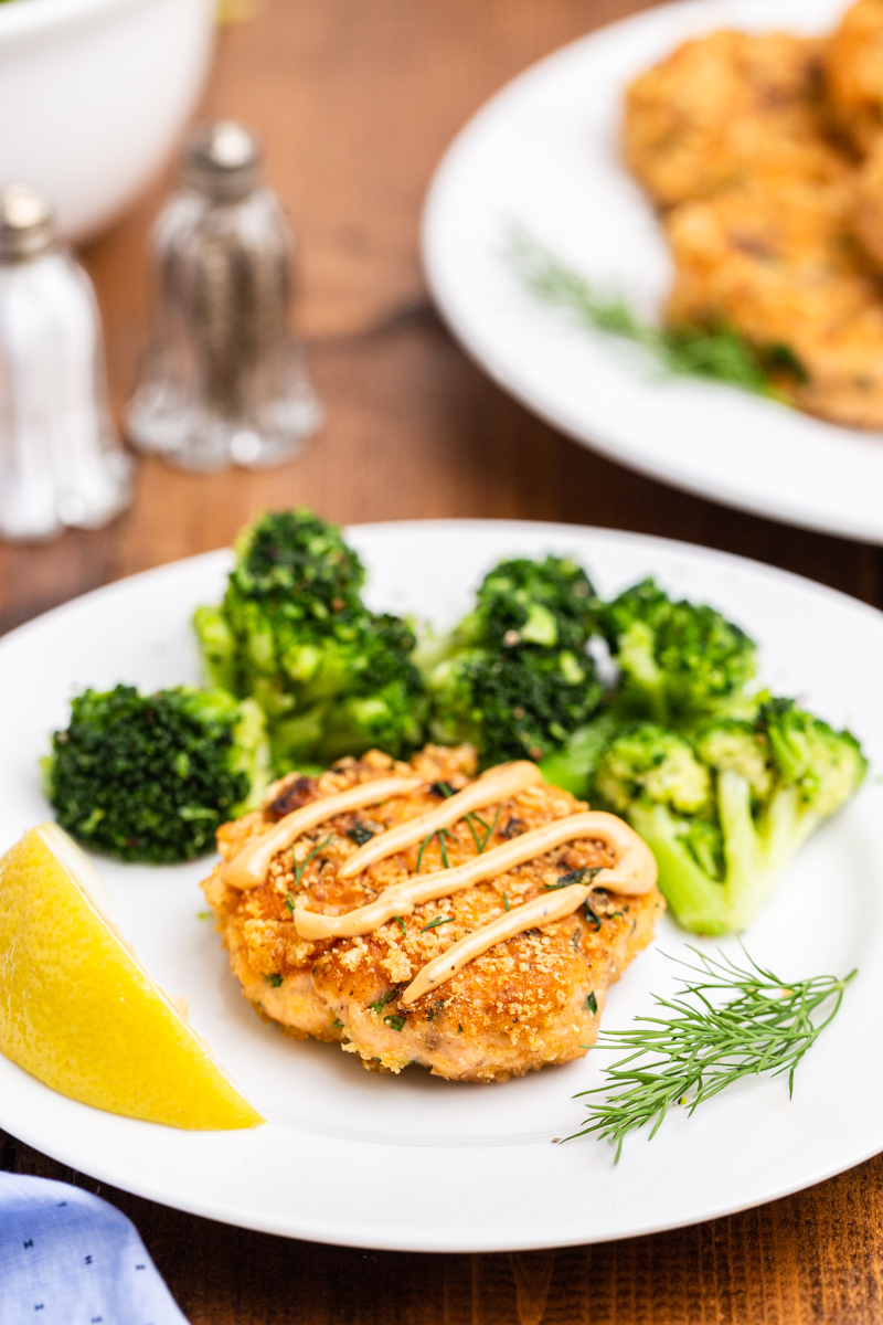 Closeup photo of a Keto Salmon Cakes (Salmon Patties) on a white plate with broccoli and remoulade sauce.