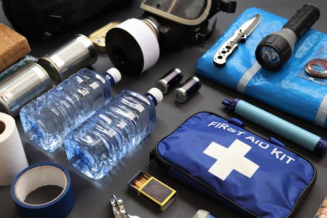 survival kit met water, gasmasker, zaklamp, zakmes, zeil