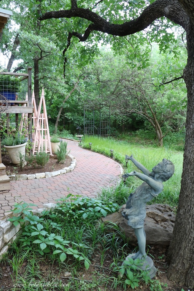 Peach French Tuteurs with statue in spring backyard garden