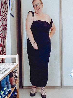 Sarah is stood up wearing a black dress with one hand on her hip she is smiling at the camera