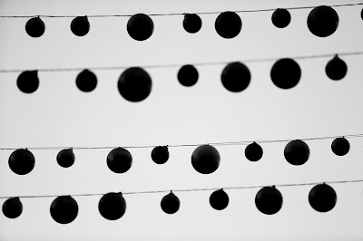 black and white image of balloons hanging in lines