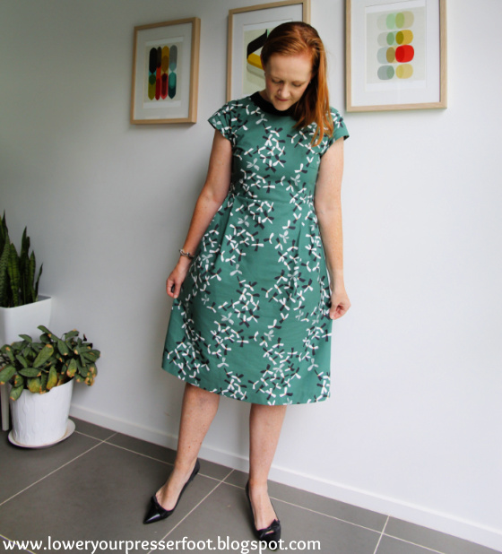 a white lady posing in a green dress spreading the skirt wide