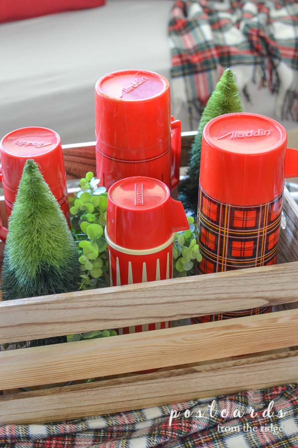 vintage red plaid thermoses and bottle brush trees in a wooden crate