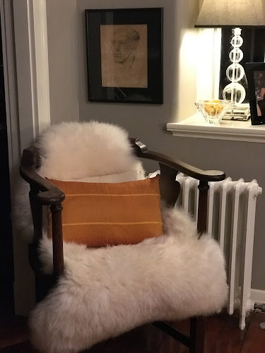 Photo of antique oak captains chair with sheepskin throw and cushions