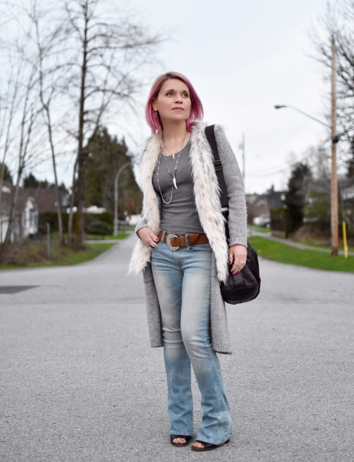 Monika Faulkner outfit inspiration - styling a tank top and flare jeans with a long cardigan and faux-fur vest
