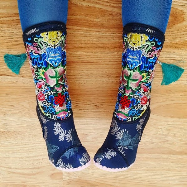 lying on floor wearing embroidered floral colourful navy boots with tassels