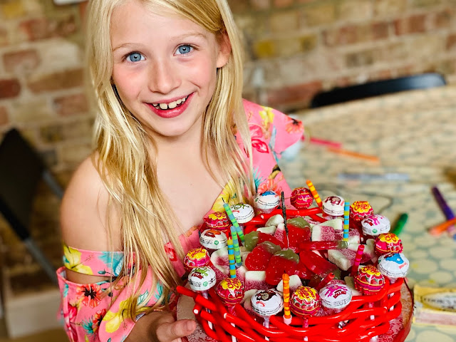 A sweetie cake with the candles blown out. It has lollipops and liquorice around the edge and is filled with sweets