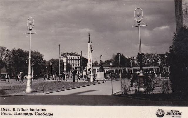 """Часы """"Laima"""" на перекрестке бульваров Бривибас и Аспазияс на """"площади Свободы"""". В сквере скульптурная композиция """"Мать, провожающая сына в партизаны"""" (или """"Проводы в партизаны"""")"""