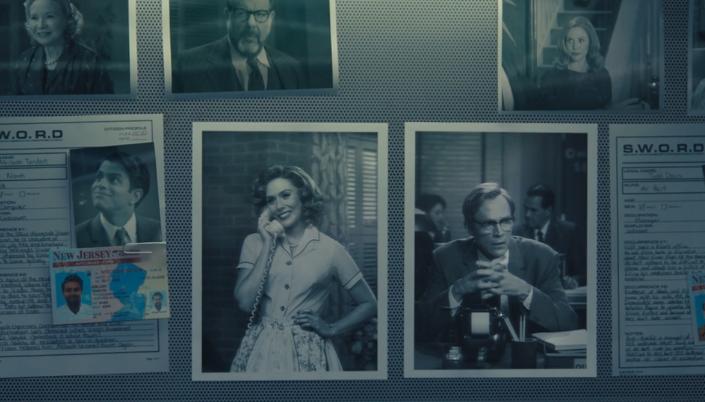 Imagem: um quadro de avisos com fotos dos personagens do mundo sitcom de Wanda Vision com suas identificações e nomes do mundo real, anotações e cópias de documentos e identidades e as fotos de Wanda e do Visão no centro.