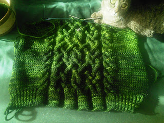 An image of a green cabled sweater-in-progress laying flat.  There is a tabby cat on the top edge of the sweater