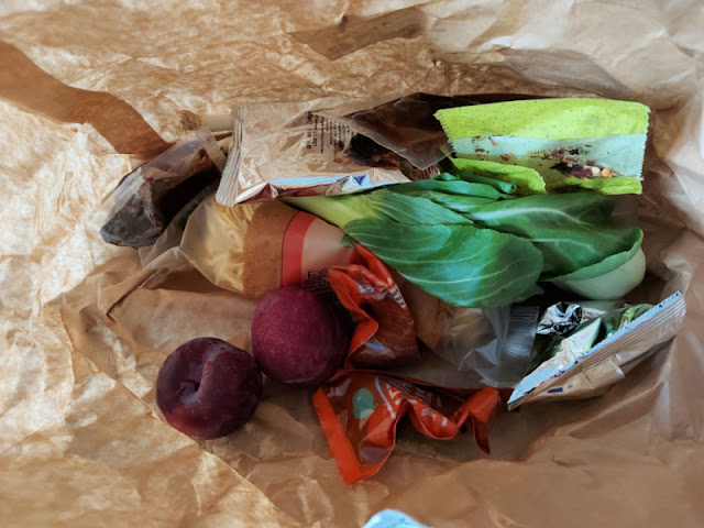 Vegetables and packets of condiments inside a brown paper bag
