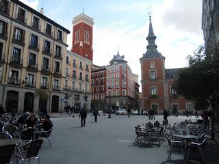 De un ángulo de la plaza se ven al fondo una de las torres del palacio y la torre de la iglesia. En primer plano las terrazas de los bares.