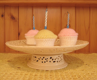 A cream, filigree-patterned, porcelain cake stand rests on a yellow filet crocheted mat. On top are three crocheted cupcakes with white bases and tops of yellow and pink. Each cupcake holds a birthday candle. The pine wood in the background is the cupboard on which the cake stand is displayed.