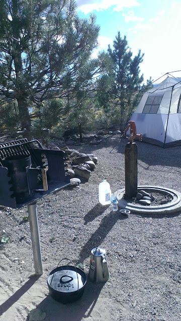 tent, charcoal grill and water area, dutch oven, and coffee pot