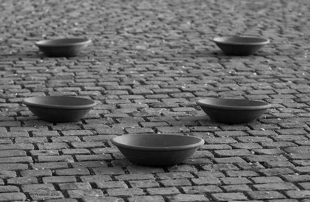 A Black and White Minimal Photo of Five Clay Pots lying on the Streets right in Front of Albert Hall Museum, Jaipur.
