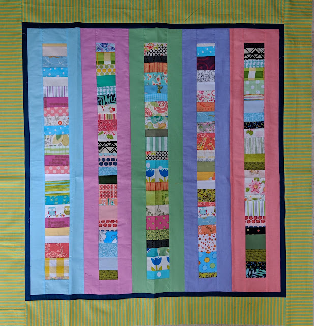Five narrow columns of Chinese Coin strips are each sashed with a different solid pastel cotton. They are enclosed by a narrow black border and a wider green and yellow striped outer border.