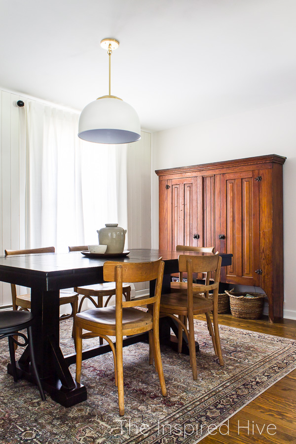 Black dining table with antique wooden chairs. Modern dome light. Large antique cabinet.