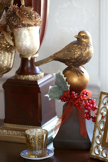 Bird finial with ribbon, holly leaves and Christmas berries and gold glitter acorns tied with ribbon dangling from the lamp.