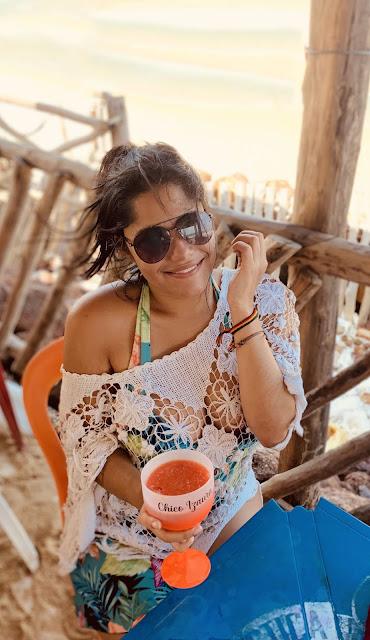 mulher sentada em um quiosque na beira da praia tomando uma caipirinha de acerola
