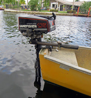 Outboard motor mounted on stern of canoe.