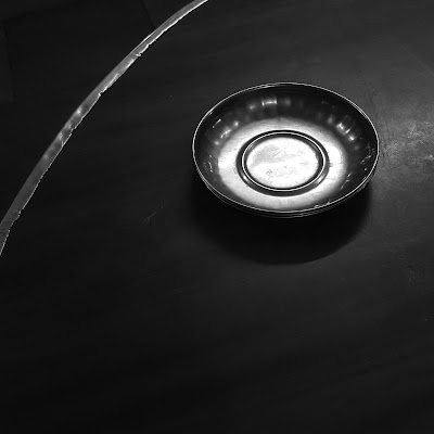 A Black and white Minimalist Photo of a metal plate and a curved line shot by Samsung Galaxy S6 Smart Phone