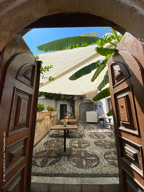 Opened wooden doors that lead to a courtyard restaurant tiled with pebbles and decorated with palm trees and bougainvillaea.