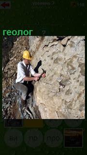 мужчина геолог в каске на скале за работой