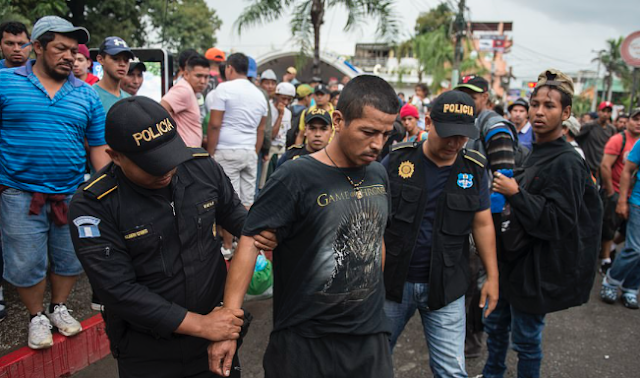More than 4,000 Honduran migrants heading for America face off against police in river town on Guatemala-Mexico border as caravan activist who angered Trump is arrested and bundled into a van by Mexican police in shocking video