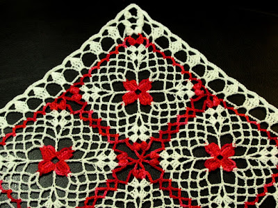 Closeup of RSS Designs In Fiber Red Flower in White Lace Square Doily